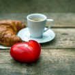Red heart candle, cup of black coffee with croissant — Stock Photo #62877939