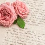 Pink rose flowers over handwritten letter — Stock Photo #67839945