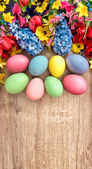 Spring flowers and colored eggs. — Stock Photo