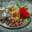 Tea, dates fruits and red rose flowers. Oriental hospitality vin — Stock Photo #79108866