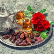 Tea, dates fruits and red rose flowers. Oriental hospitality con — Stock Photo #79109484