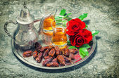 Red rose flowers with tea and dates fruits. Ramadan. Vintage sty — Stock Photo