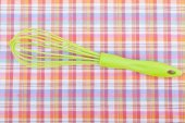 Whisk on a checkered tablecloth. — Stock Photo