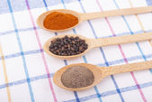 Whole and ground pepper in a wooden spoon on the tablecloth. — Stock Photo