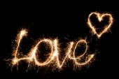 Inscription Love and heart of sparklers. — Stock Photo