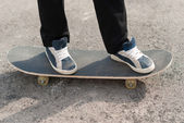 Skateboarder feet in sneakers on a skateboard. — Stock Photo