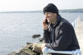 Man talking on phone at end of breakwater in bay — Stock Photo