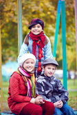 Happy schoolkids sitting in park — Stock Photo