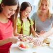 Daughters making apple pie with mother — Stock Photo #53810337