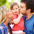 Careful parents kissing their daughter — Stock Photo #53810407