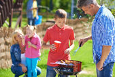 Big family frying sausages — Stock Photo