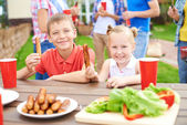 Children eating grilled sausages — Stock Photo