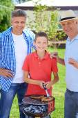 Grandpa, father and boy grilling sausages — Stock fotografie