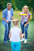 Parents playing frisbee with daughter — Стоковое фото