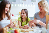 Girls and mother making patties — Stock Photo