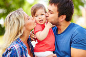 Careful parents kissing their daughter — Stock Photo