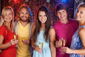 Happy young friends holding flutes — Stock Photo