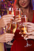 Hands cheering up with champagne — Stock Photo