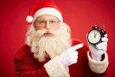 Santa Claus pointing at clock — Stock Photo