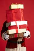 Santa Claus holding pile of giftboxes — Stock Photo