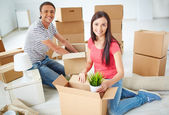 Young couple unpacking boxes — Stock Photo