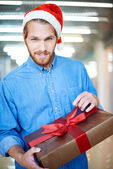 Young man unpacking Christmas present — Stock Photo