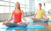 Girl and guy meditating — Stock Photo