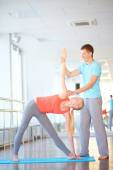 Female doing physical exercise with trainer — Stock Photo