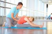 Female doing physical exercise with trainer — Stok fotoğraf