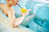 Girl drinking lemonade in swimming pool — Stock Photo