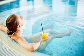 Pretty girl relaxing in swimming pool — Stock Photo