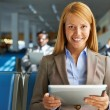 Woman with touchpad sitting in airport — Stock Photo #55417643