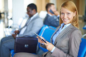 Female employee with touchpad at the airport — Stock Photo
