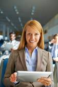 Woman with touchpad  in airport — Stock Photo