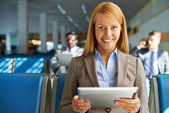 Woman with touchpad sitting in airport — Stockfoto