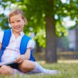 Child with backpack sitting on grass — Stock Photo #55466557