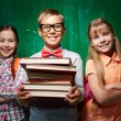 Schoolboy with stack of books and two girls — Stock Photo #55466931