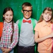 Schoolkids standing by the blackboard — Stock Photo #55466987