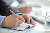 Male hand with pen making notes — Stock Photo