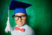 Elementary learner in eyeglasses and graduation hat — Stock Photo