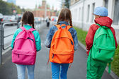 Schoolkids with colorful rucksacks — Stock Photo