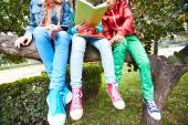 Schoolkids sitting on tree  and reading — Stock Photo