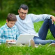 Man and son using laptop  in  park — Stock Photo #55473135