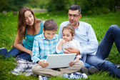 Family using laptop in park — Stock Photo