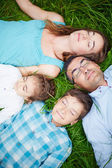 Family relaxing on grass — Stock Photo
