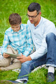 Father and son using digital tablet outdoors — Стоковое фото