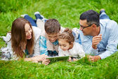 Family lying on grass with touchpad — Stock Photo