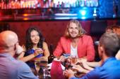 Friends with drinks relaxing at party — Stock Photo