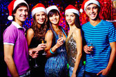 Friends in Santa caps toasting at party — Stock Photo