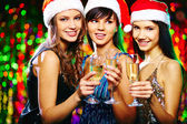 Girls in Santa caps toasting — Stock Photo